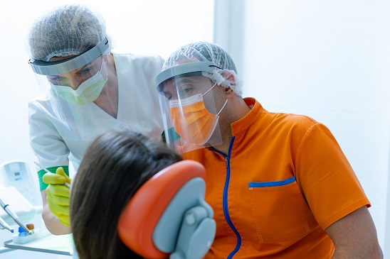 dentist and technician wearing covid-19 protection