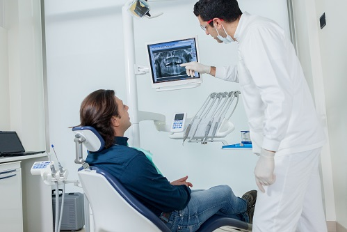 dentist showing patient image on monitor